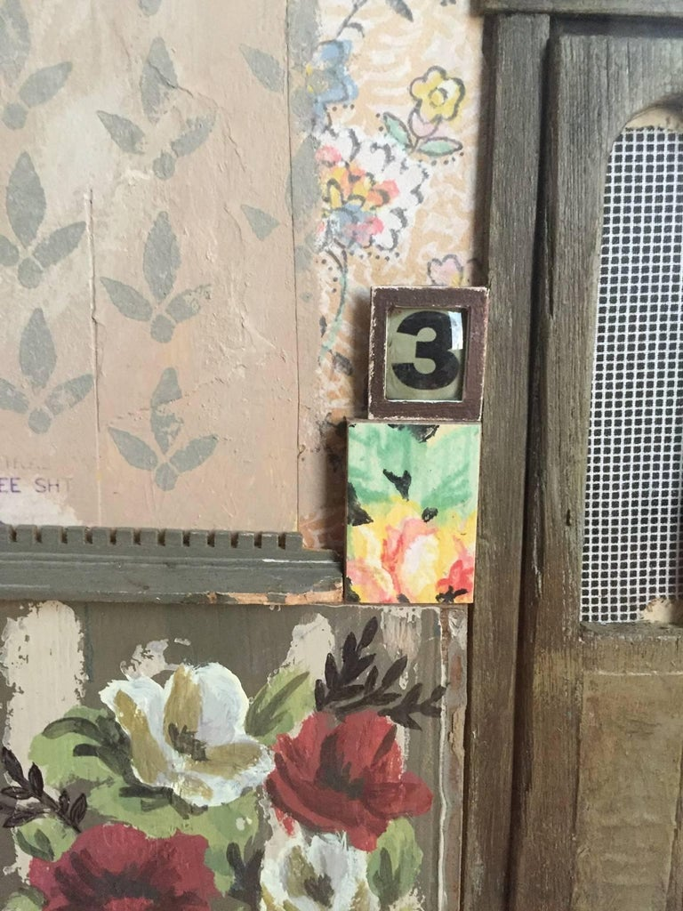 """Chelsea Revelle's """"Mrs. Russell"""" is a 15.5 x 12 inch mixed media shadow box assemblage that incorporates disassembled dollhouse parts juxtaposed with vintage image transfers of female figures disappearing into wallpaper layers. Adorned with a white"""