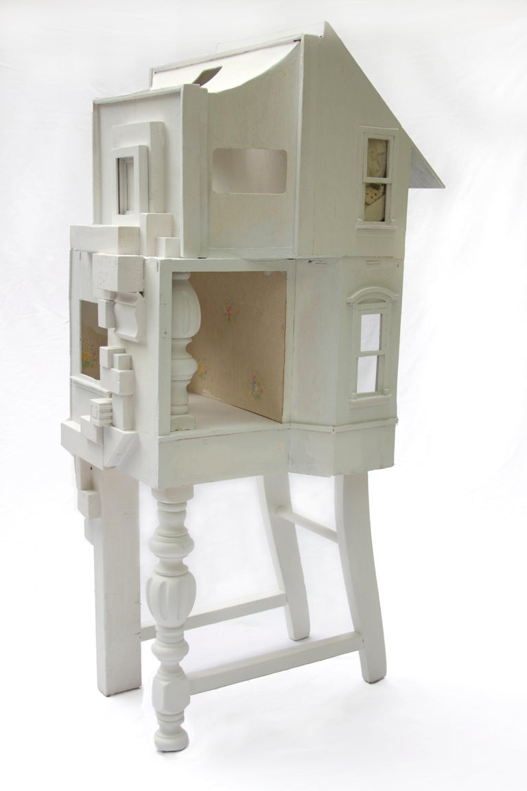 "Chelsea Revelle's ""Gilded Serenity"" is a 19 inch wide x 38 inch tall x 17 inch deep 3D assemblage and is part of her ""Fragility of Silence"" series. The piece is made up of disassembled dollhouses and chairs, juxtaposed into a free-standing sculpture"