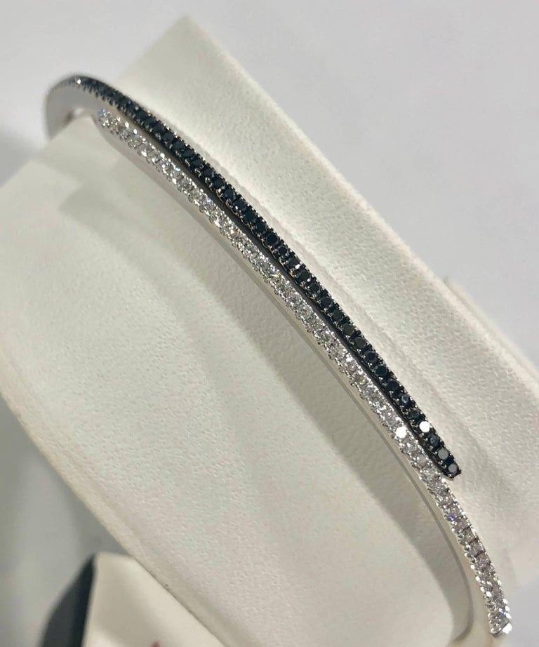 Cherie Dori 18 karat white gold and diamond cuff bracelet. This unique piece is created in 18 karat white gold, weight equaling 15.8 grams/ 10.1 dwt. There are 47 full cut round black diamonds equaling .25 carat total weight, and 47 full cut round