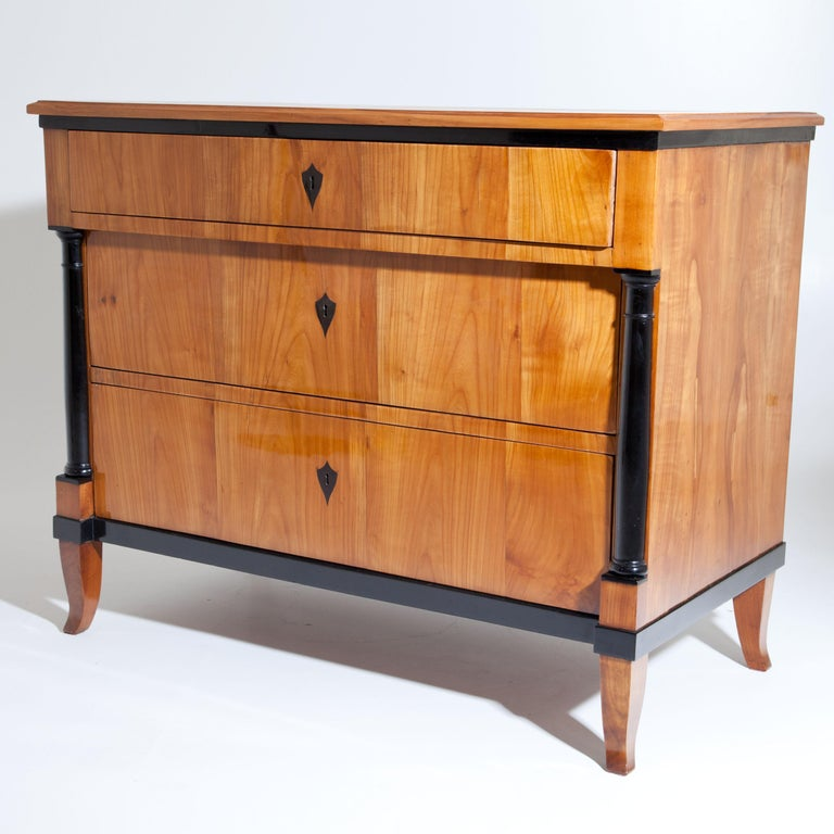 Three-drawered Biedermeier chest of drawers on curved feet with lateral ebonised columns, supporting the top drawer. The escutcheons are ebonized, as are the upper and lower edges of the body. Cherry veneer. The chest of drawers has been expertly