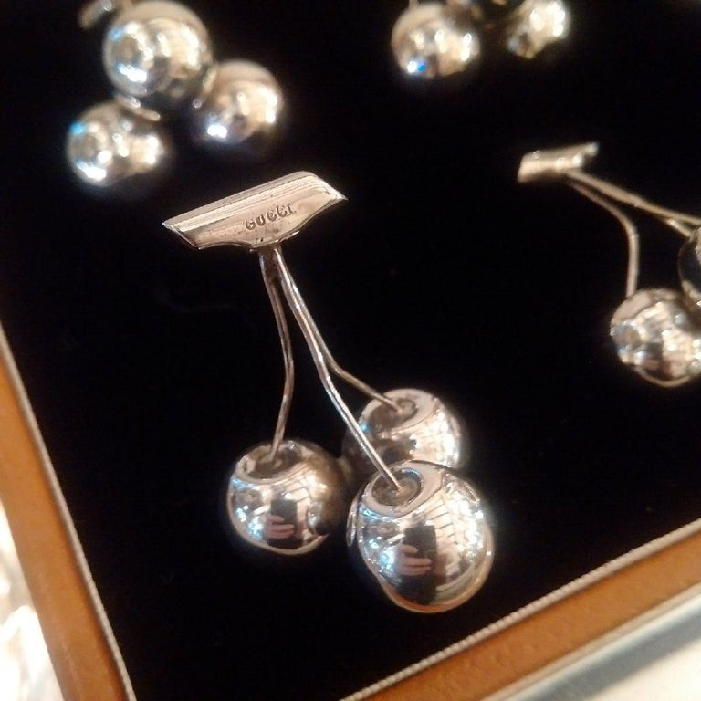 A set of six Sterling silver place-card or menu holders in the form of three cherries with stalks, each holder bearing Gucci hallmarks to the stems, upon which the cards rest. Gucci produced a range of figurative design menu holders in the 1960s,