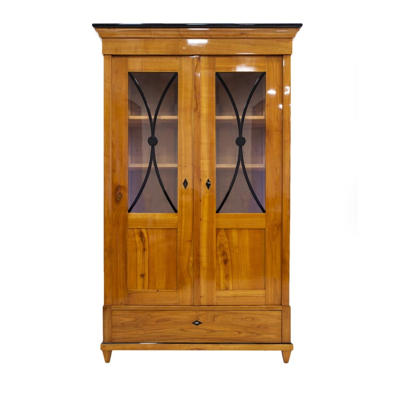 This beautiful cherrywood vitrine comes from Germany from 19th century (the Biedermeier period). The construction is made of solid cherrywood. The piece features practical shelves in the main sections and a spacious drawer at the bottom. It was