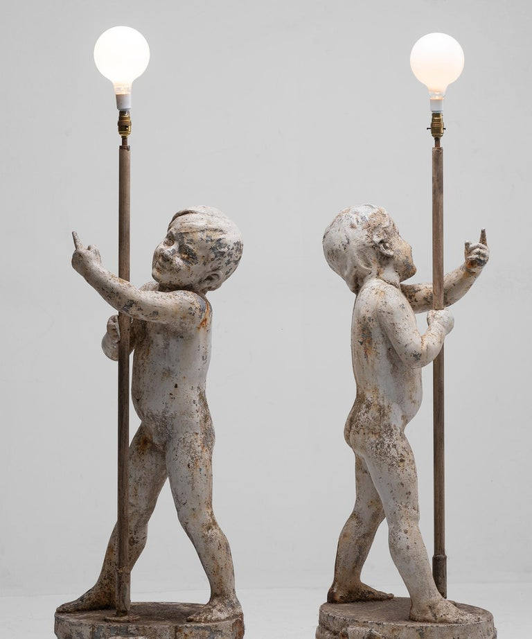 Cast iron floor lamps with standing cherubic boys on raised circular base.