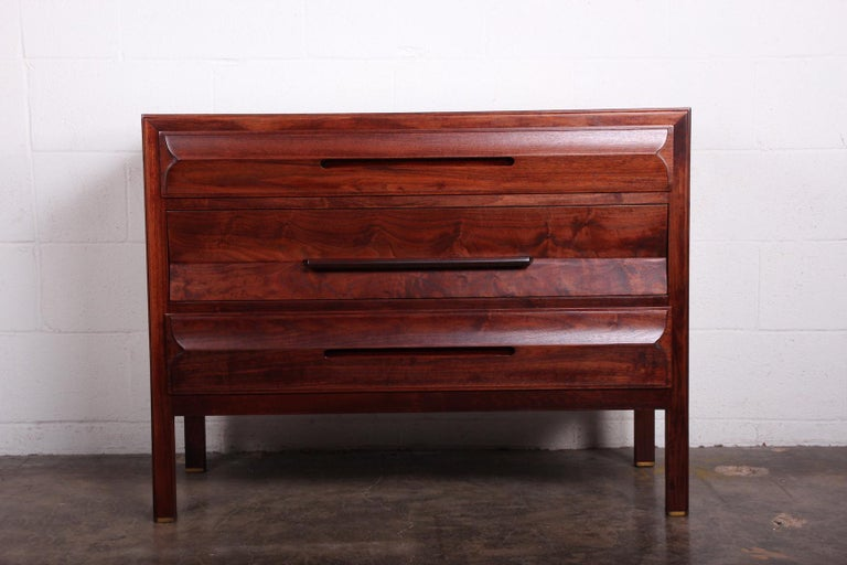 A walnut dresser with rosewood handle and brass feet. Designed by Edward Wormley for Dunbar.