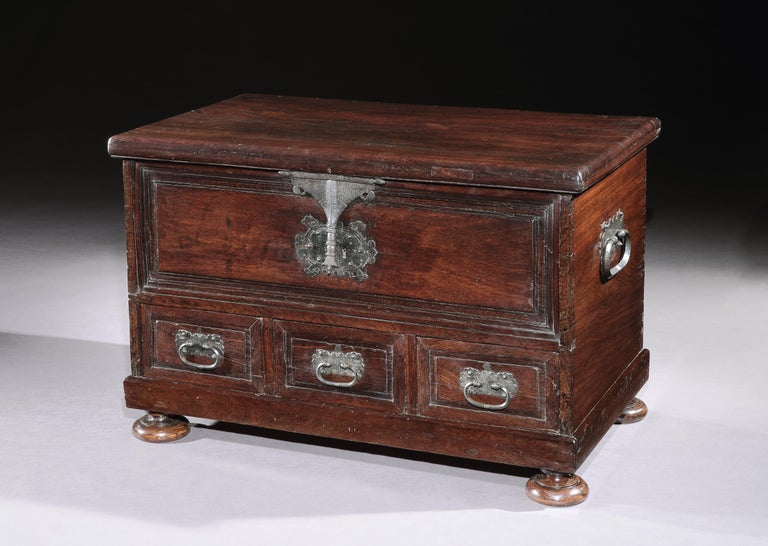 This striking chest is made from a Brazilian hardwood which I have not been able to identify. The color and figuring of the timber together with the Classic form and ornamentation supplemented by the elaborate ironwork create a simple, bold