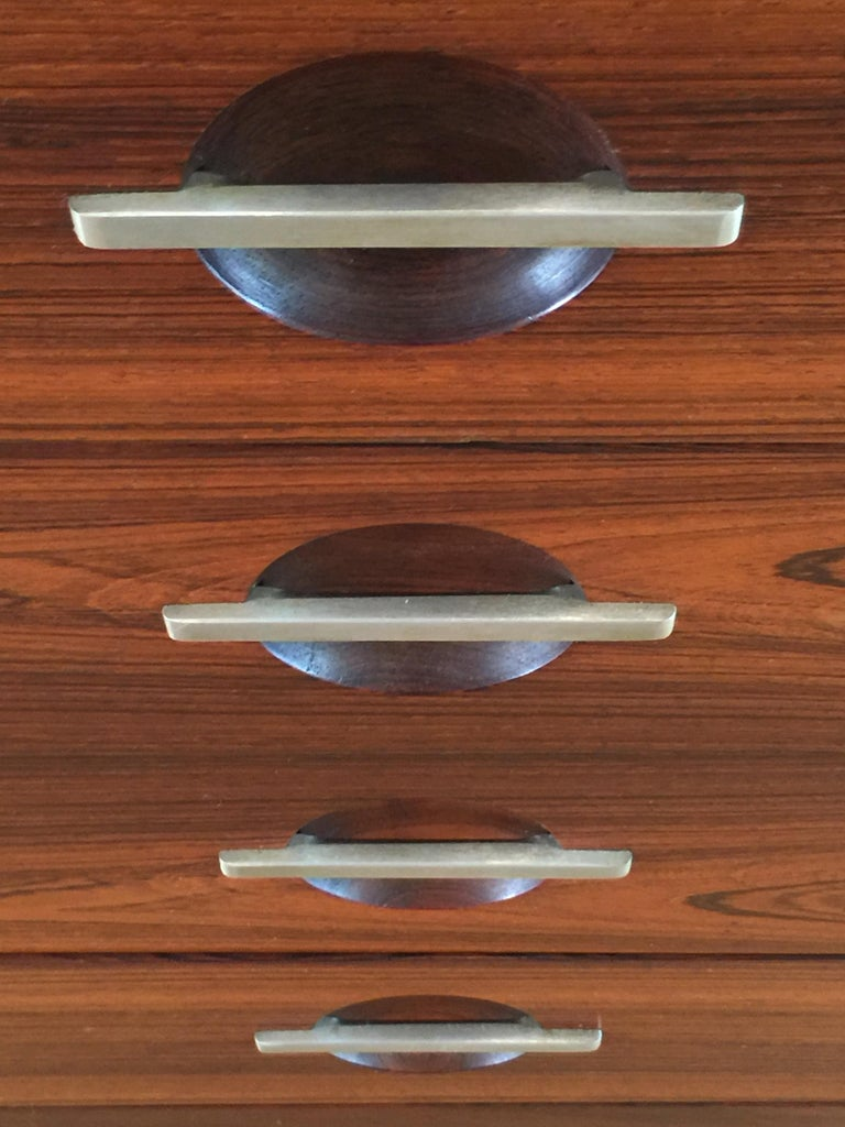 An exceptionally handsome chest of drawers in polished palisander contrasting with brushed stainless steel mounts. The drawer pulls are brushed steel across recessed hemispheres, and the stainless steel legs terminate in palisander 'feet'.  Illus.