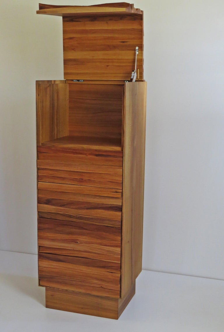 Solid wood piece of furniture with a modern expression The front is made of split wood - the wood is split with the ax - the individual logs are then glued. This is how this living wood is created.  The dresser has a flap on top of storage space