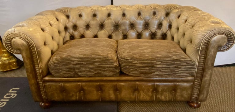 Chesterfield leather upholstered loveseat Sofa. This more than likely English Chesterfield has bun feet supporting a worn leather frame. The cushions are done in a designer fabric. ELS.