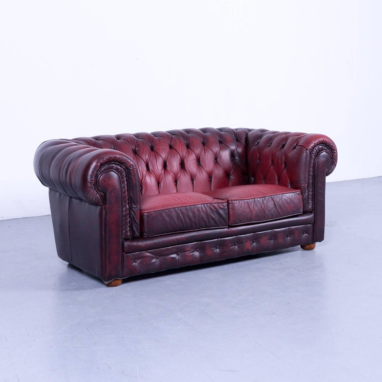 Chesterfield two-seat sofa red leather couch vintage retro rivets, made for pure comfort and elegance.