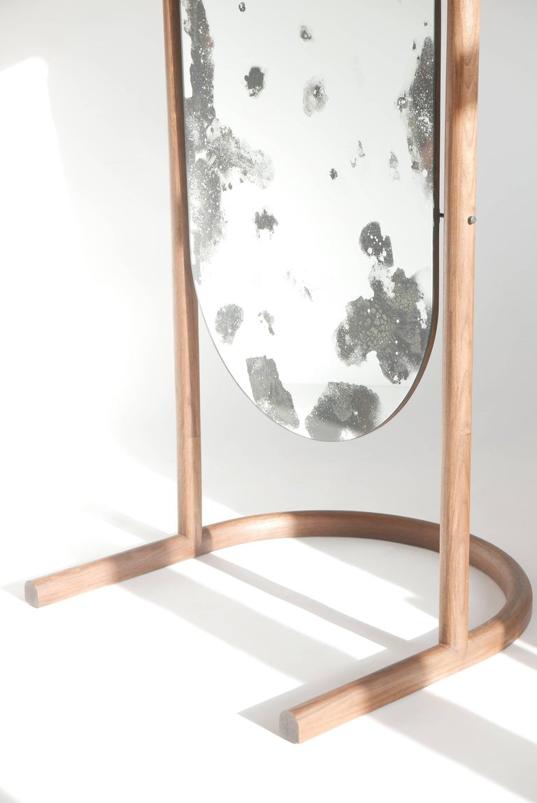 This custom Cheval style pivoting floor mirror is a freestanding version of our wall-hanging Oxbow mirror.    Our Oxbow mirror combines a perfect arc, mystic mirror effects, and a simple platform for display or function. The oxbow form is derived