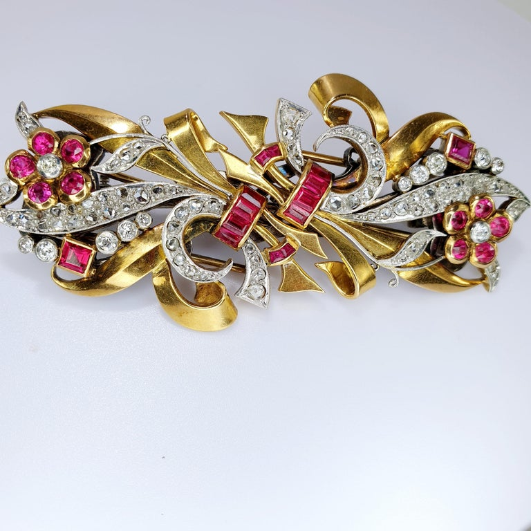 This beautiful Chevalier epoque  1940's clips can be worn separately or together by its custom fitting.  The diamond and gold ribbon swirl iand nests ruby colored gems. The brooch is 18k rose gold  and fitting is 18k white gold.  Can be used in