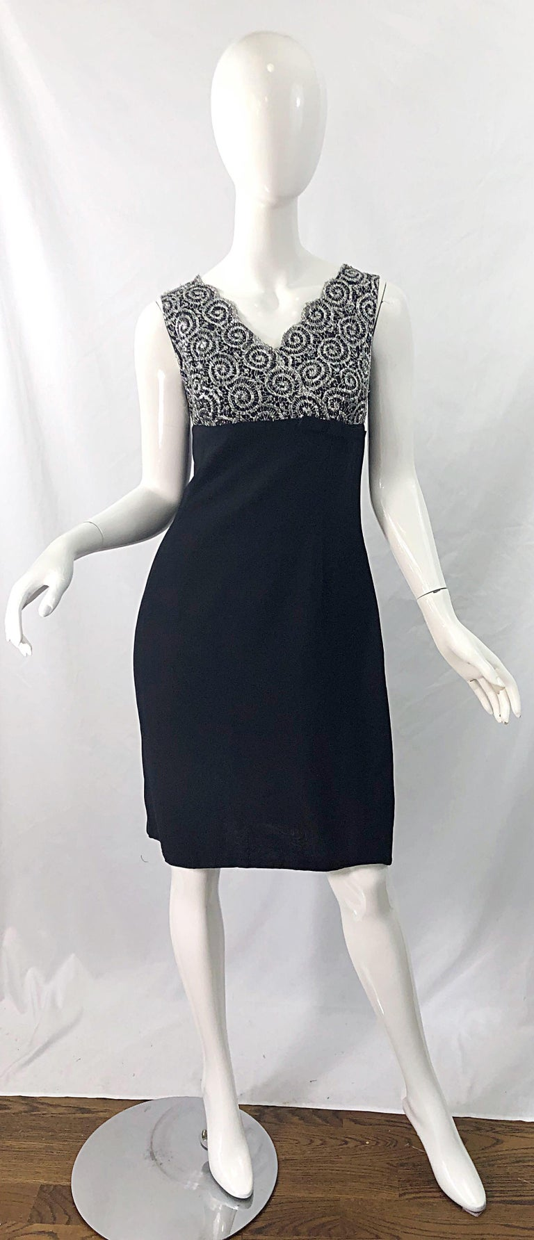 Chic 1960s black rayon crepe and silver metallic lace vintage sheath dress ! Features an empire style waist with bow at side left waist. Swag detail at center back. Full metal zipper up the back with hook-and-eye closure. The perfect little black