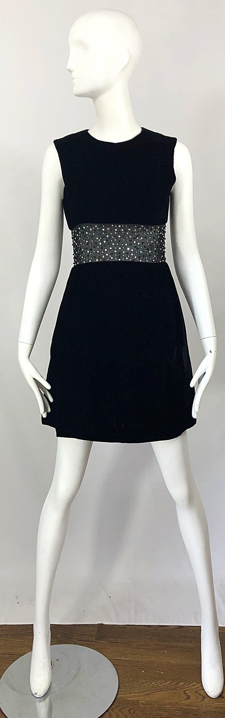 Chic 1960s black velvet cut-out A-Line dress! Features soft black velvet with a sheer black mesh cut-out at waist. Over 100 hand-sewn rhinestones and beads throughout the sheer paneling. Hidden metal zipper up the back with hook-and-eye closure.