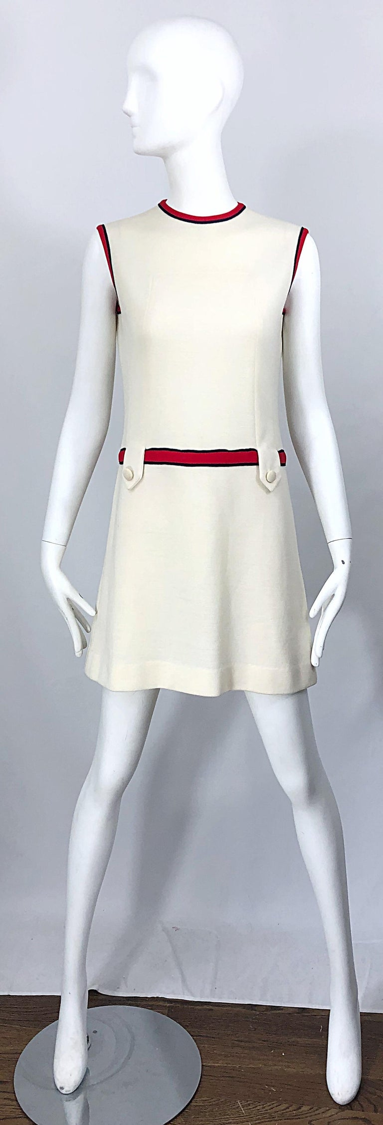 Chic 1960s ivory, navy blue and red knit scooter / shift dress! Features soft ivory knit that has plenty of stretch. Two loops and buttons at each side of the front waist. Hidden metal zipper up the back with hook-and-eye closure. Great with
