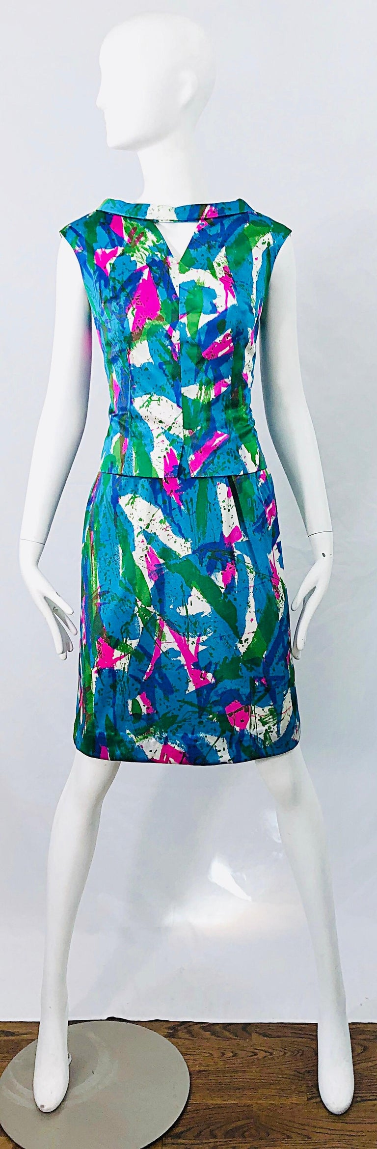 Chic mid 60s vibrant colored abstract print two piece sheath dress and top ! Features vibrant neon colors of pink, blue, turquoise, green and white throughout. Top features center cut-out at top center neck. Dress has a tailored bodice with nipped