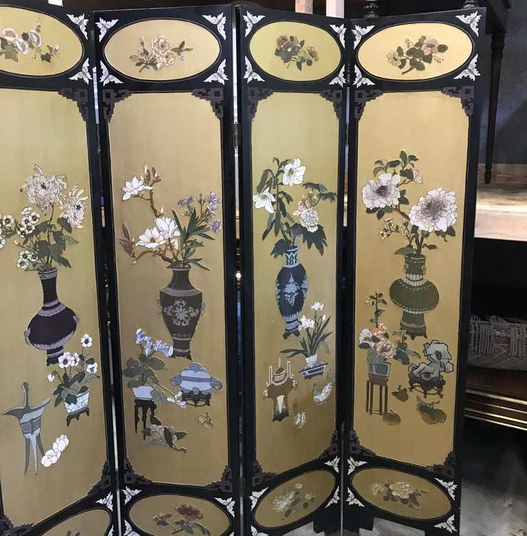 The Coromandel screen in black with large gilt cartouches with images of Chinese porcelain vases with floral decoration. The back in black lacquer with engraved decoration. 