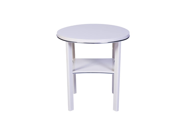 This chic Art Deco side table features a simple design with chrome line detailing finished in a luscious high gloss white lacquer.