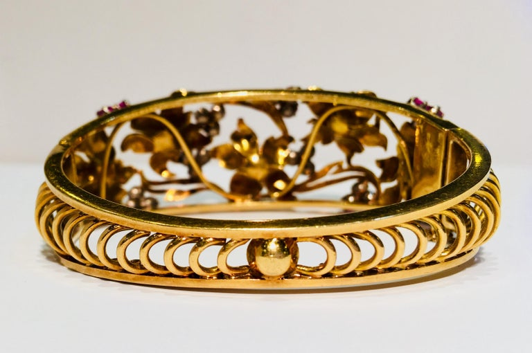 Gorgeous, handmade, 18 karat yellow gold floral estate bracelet from the early 1900s has the graceful flowing lines of stylized, intertwined flowers and leaves popularized by the Art Nouveau movement.  Tapered, hinged bangle bracelet features 5