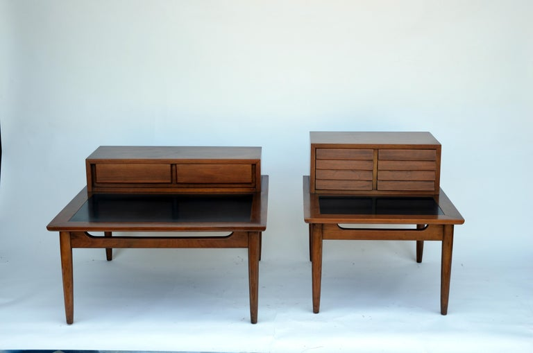 Two chic matching of vintage Mid-Century Modern end tables featuring louvered drawers and a bottom tier with a black laminate top. A sleek two-tier design made of walnut that sits on top of four tapered legs. Quality construction with four sculpted