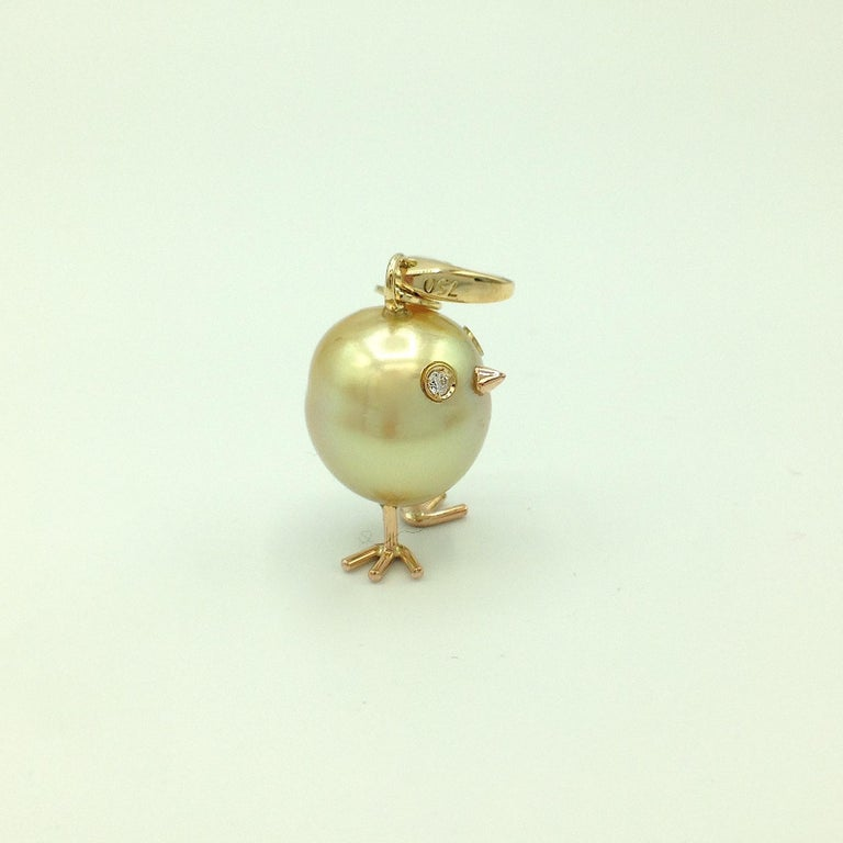 Chick Australian Pearl Diamond Yellow Red 18Kt Gold Pendant/Necklace or Charm A beautiful oval shape Australian pearl has been carefully crafted to make a chick. Its color is natural. He has his two legs, two eyes encrusted with two white diamonds