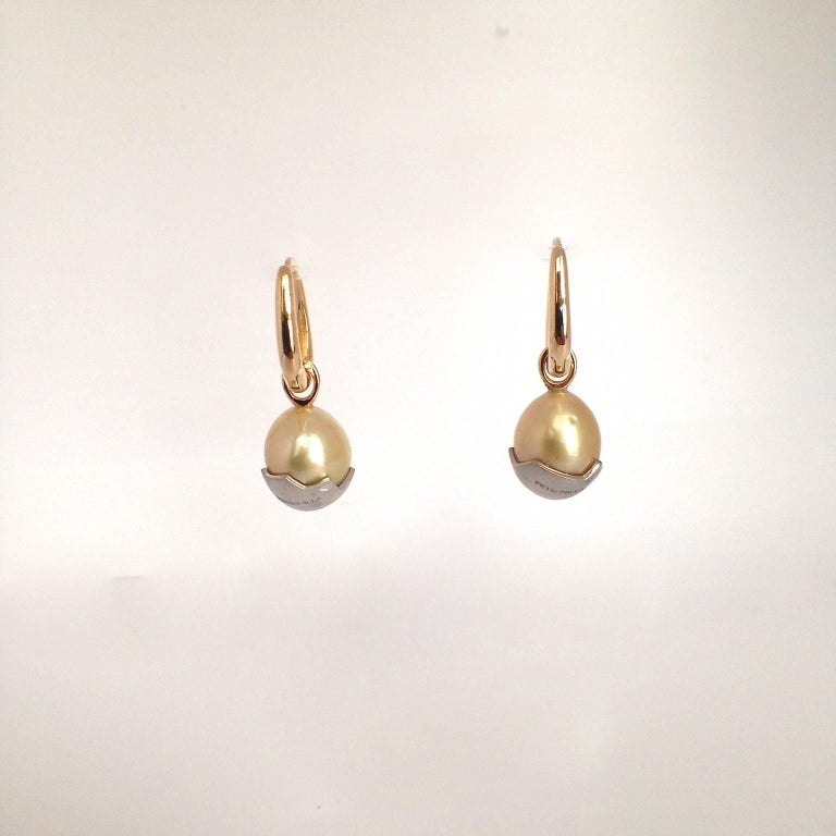 These earrings are composed of two elements. There are two simple yellow gold ring earrings that can be worn alone and then there are two small pendants that can be slipped into the rings and worn together. The two pendants are two Australian pearls