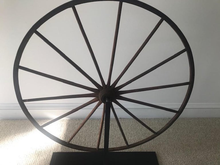 Bring some folk art into your home with this period wooden wagon wheel. The diminutive size suggests that it was originally on a child's wagon. It has been expertly mounted a custom steel stand, allowing it to be placed on a fireplace, mantle or