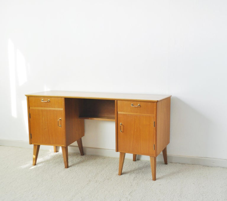Childs executive desk in ash with bowed top with vibrant wood grain, restored and lacquered. Front with one drawer and cabinet each side with brass pull handles. Leg clearance 44.5 cm, features a little shelf under the top.  Dimensions: H 64 cm x