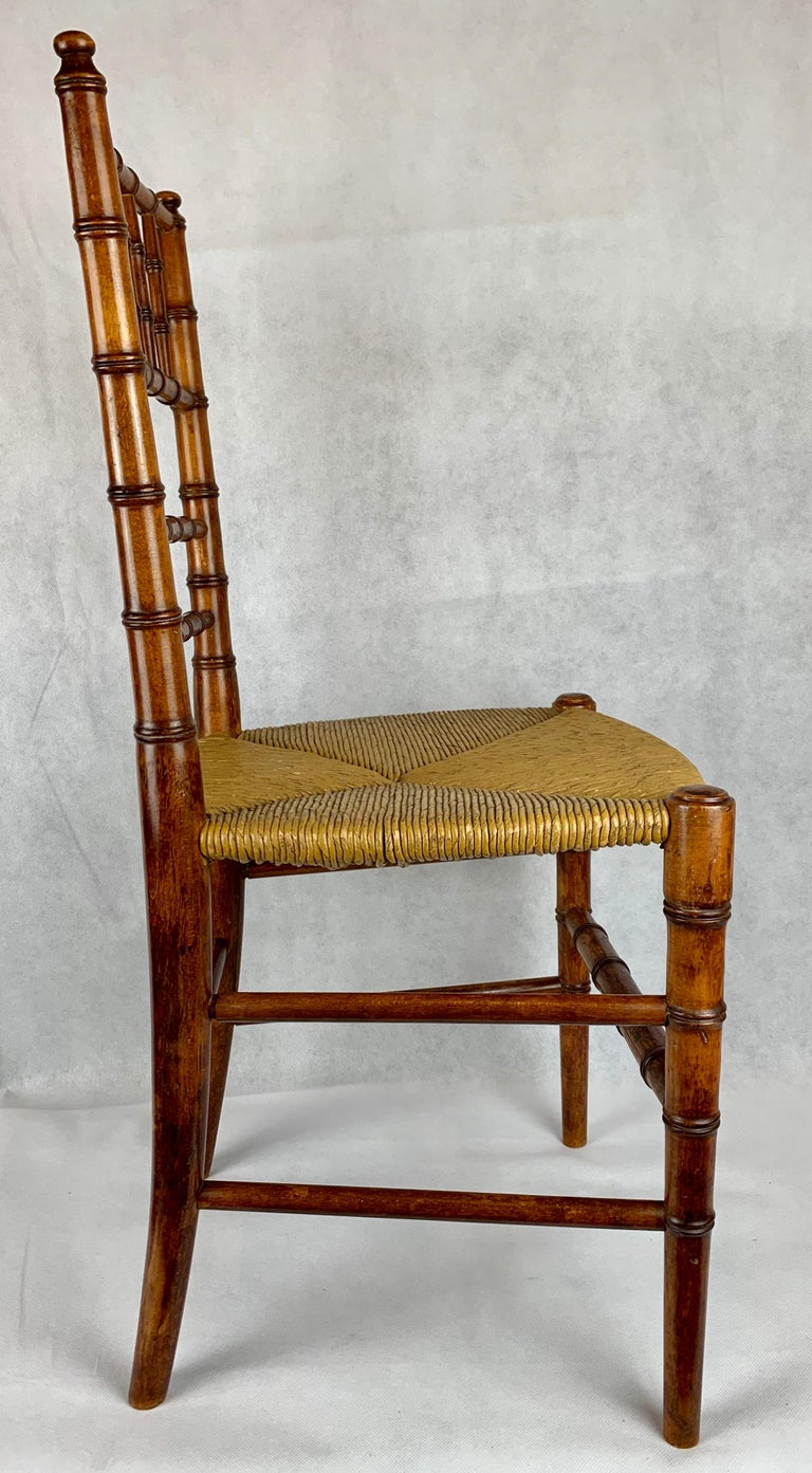 Child's hand turned faux bamboo side chair with rush seat and six stretchers.  (Adorable) . Also useful in a powder room to hold towels, magazines, etc. Structurally very strong even for an adult. Hand polished in our workshop.  The seat height is