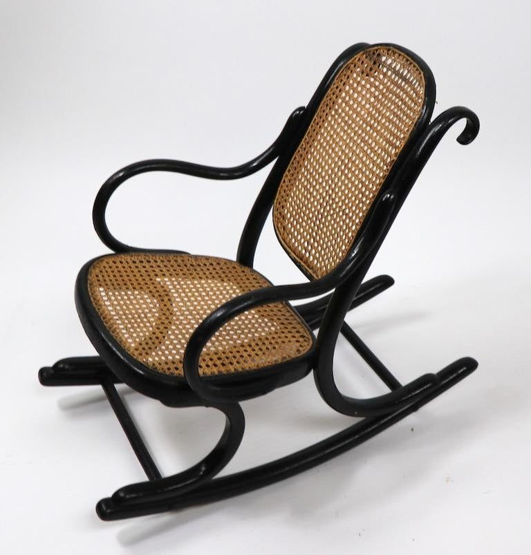 Childs rocking chair by Thonet. This example is in good overall condition, it shows some minor loss to base of backrest panel. Frame. Black finish frame, with caned seat and back. Measures: Seat H 12 x arm H 16 inch.