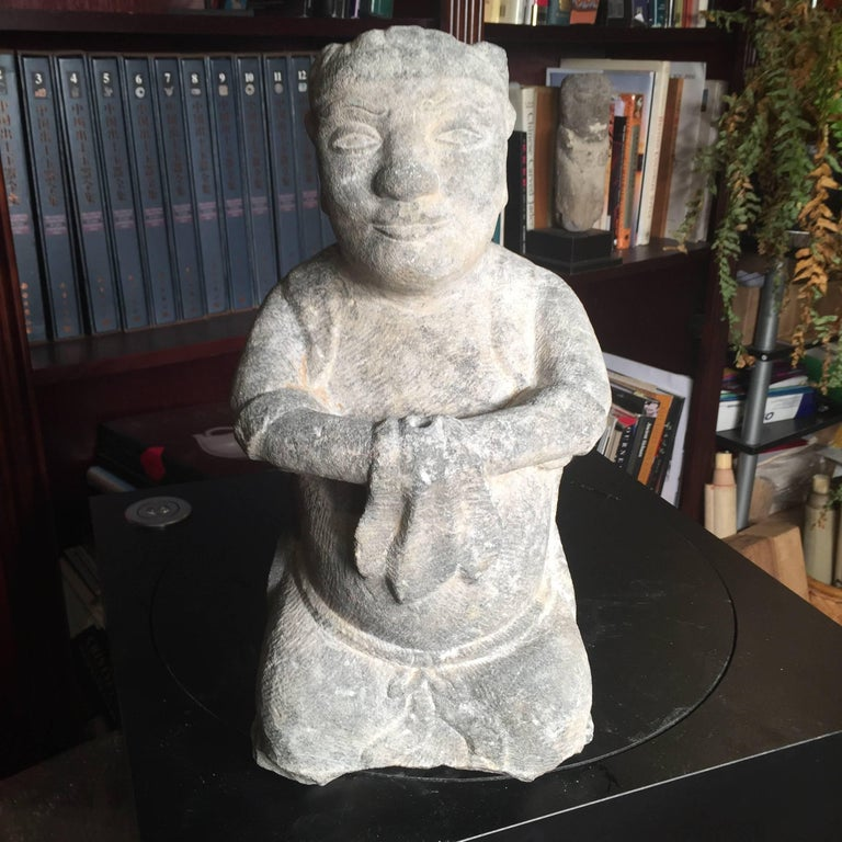 China, a large hand carved effigy of a seated attendant, limestone, Qing dynasty 1644-1912.   Dimensions: 15.5 inches tall and 7.5 inches wide and 5.5 inches deep  The hand carved figure shown on its haunches with a naturalistic servitude