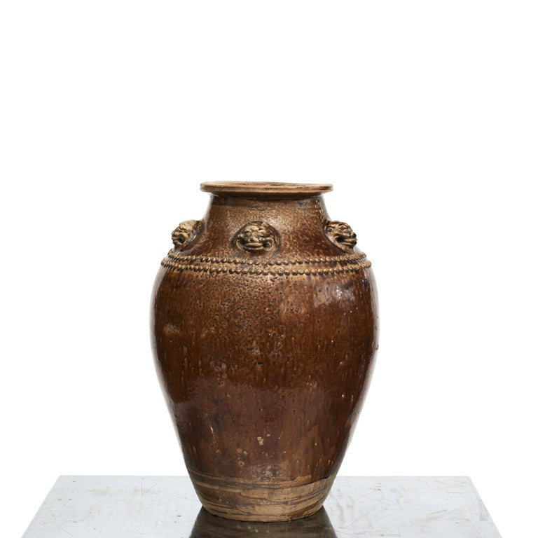 A fine and large Chinese brown ochre glazed stoneware storage jar, commonly known as a Martaban or Martavan jar. Shoulders decorated with pearls and five lion heads molded in relief, China, mid-19th century. A beautiful and fascinating example of