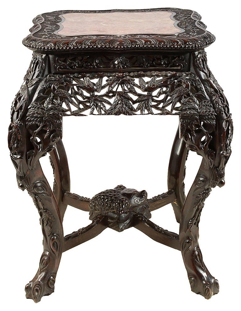 A very good quality 19th century Chinese hardwood stand, having inset rouge marble top, wonderful hand carved palm leaves and exotic bird decoration, raised on tree like cabriole legs, united by an X-stretcher with a carved mythical creature to the