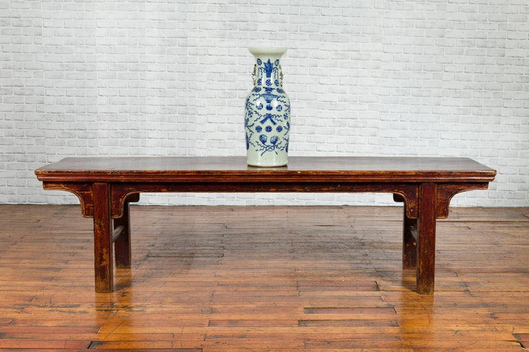 A Chinese Qing Dynasty period coffee table from the 19th century, with nicely distressed patina. Created in China during the Qing Dynasty, this low table, originally used as a bench, features a rectangular single plank top sitting above a simply
