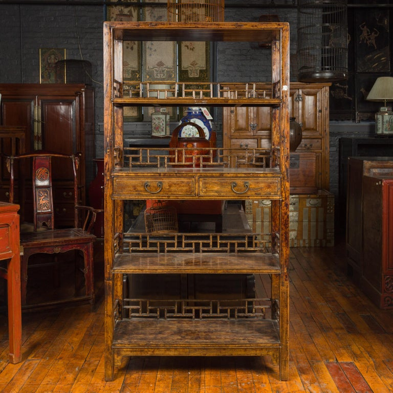 A Chinese Qing Dynasty period stained elm bookcase from the 19th century, with fretwork sides, open shelves and two drawers. Crafted in China during the 19th century, this elm bookcase features a linear silhouette presenting open shelves, each