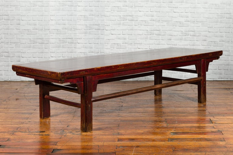 A Chinese Qing dynasty period painting table from the 19th century, with nicely weathered patina. Created in China during the 19th century, this Qing painting table will make for an excellent coffee table. A rectangular top with central board sits
