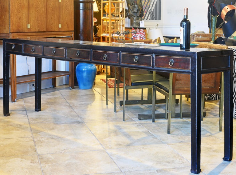 This extra long Chinese console table or altar table dates to the late 19th century and has been gracefully restored. It features a lacquered top above 7 short wood color drawers resting on square Ming style legs. The table looks good from both