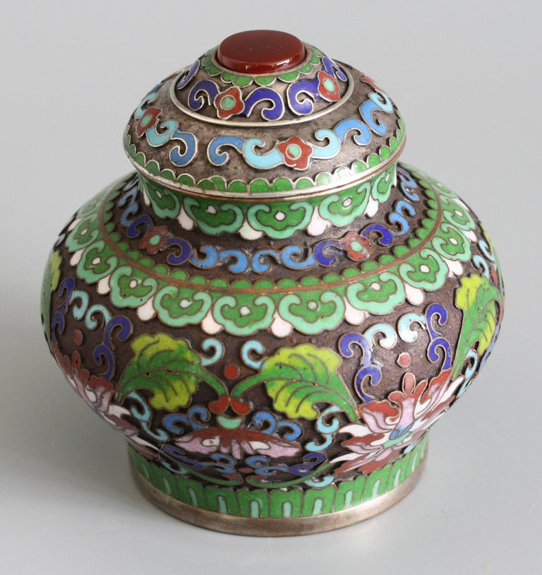 A very fine Chinese silver plated lidded cloisonne pot mounted with a polished carnelian dating from the early 20th century. This elegant pot stands on a narrow rounded base with a squat rounded body and short funnel neck with a fitted domed cover