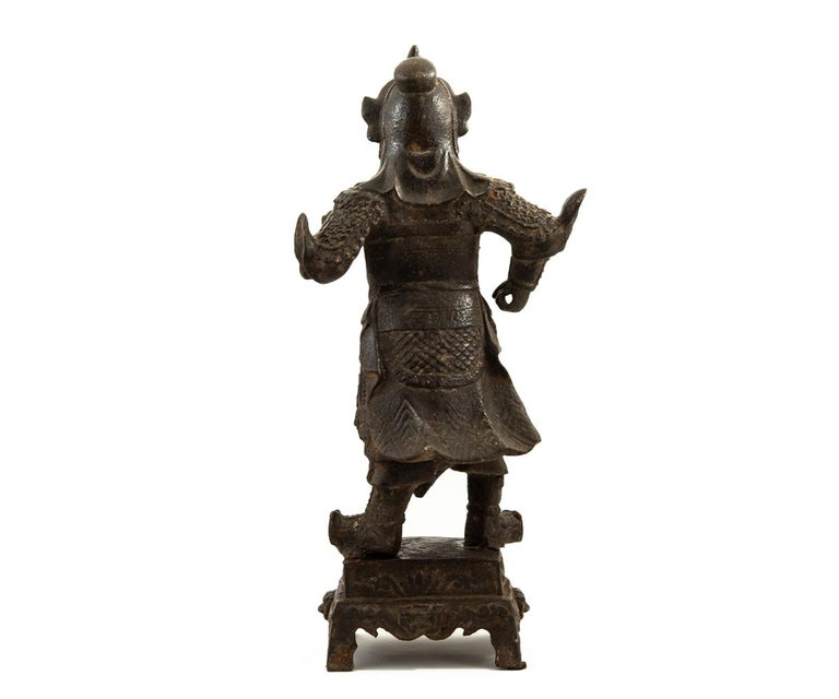 Offered is this authentic Chinese antique Ming dynasty (1368-1644) iron figure depicting the deity, Guandi, standing in armored robes and donning his helmet while stroking his beard and standing upon a pedestal base with a four-character mark.