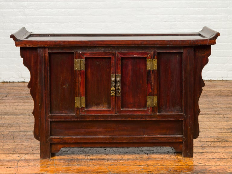 A Chinese Ming Dynasty style red rose butterfly console cabinet from the 19th century, with everted flanges, double doors and carved panels. Crafted in China during the 19th century, this small red rose console features a thin rectangular top with