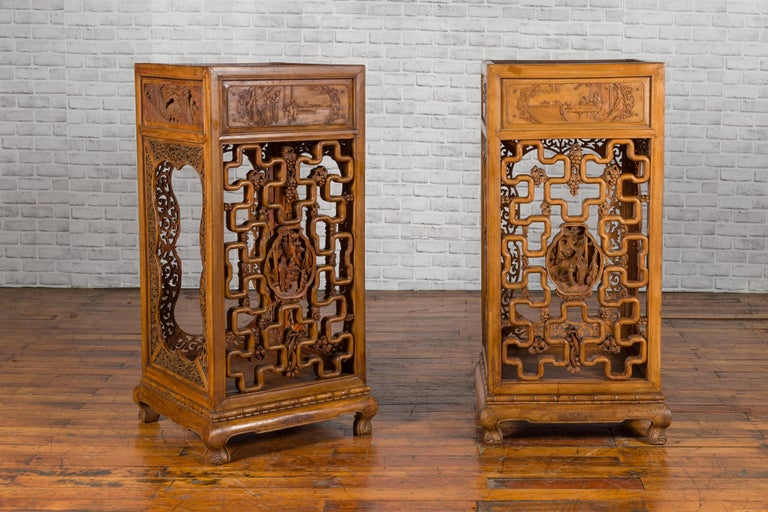 A Chinese antique pedestal from the early 20th century, with openwork motifs and hand carved court scenes. We currently have two available, priced and sold individually $2,500 each. There is a slight variation in their color, as shown in the photos.