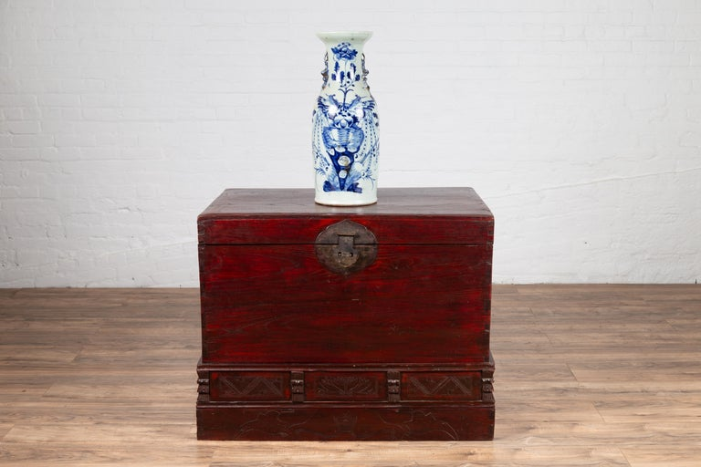 An antique Chinese red lacquered trunk from the early 20th century, with incised and carved motifs. Born in China during the early years of the 20th century, this handsome trunk boast a deep red color that captures our eyes immediately. Presenting a