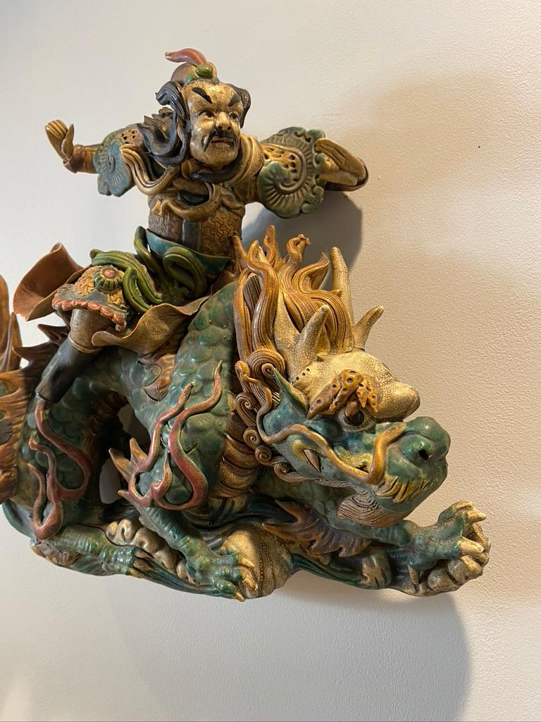 This handmade and hand glazed, painted roof tile is of pottery depicting a warrior riding a large dragon Qing dynasty.