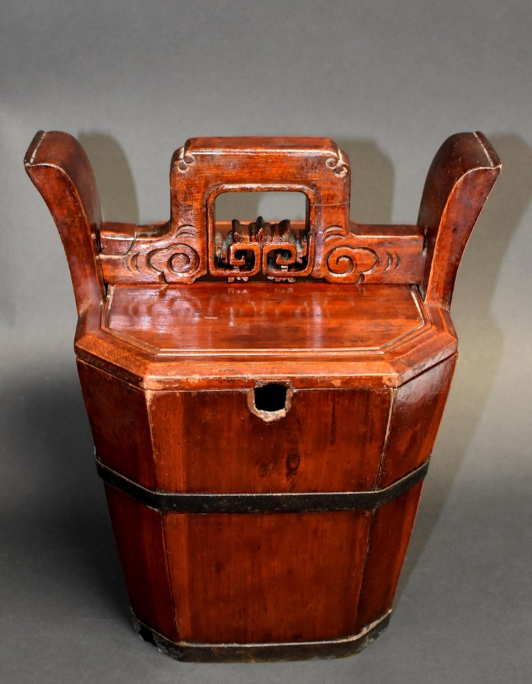 A beautiful 19th century wooden basket designed for holding and carrying a teapot. The handmade hexagonal basket's 6 sides are held together by 2 solid bronze bands. Above the lid lies a carved horizontal bar which acts as the lock to the basket.