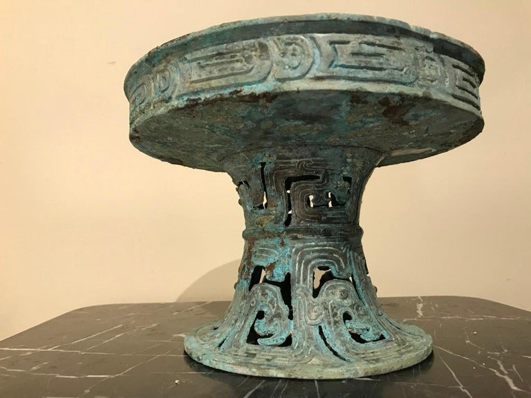 A Chinese bronze bowl on stand in the form of a tazza with wonderful verdigris patina. Warring States style (2-3rd century BC). The dish top bordered with incised decoration, the base with openwork and incised archaistic designs.
