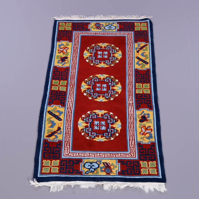 A Chinese Art Deco oriental rug offers wool construction with central triple medallions on red ground, complementing border with garden elements including butterflies and stylized flowers, circa 1940  Measures - 71'' H x 36.25'' W x .5'' D.