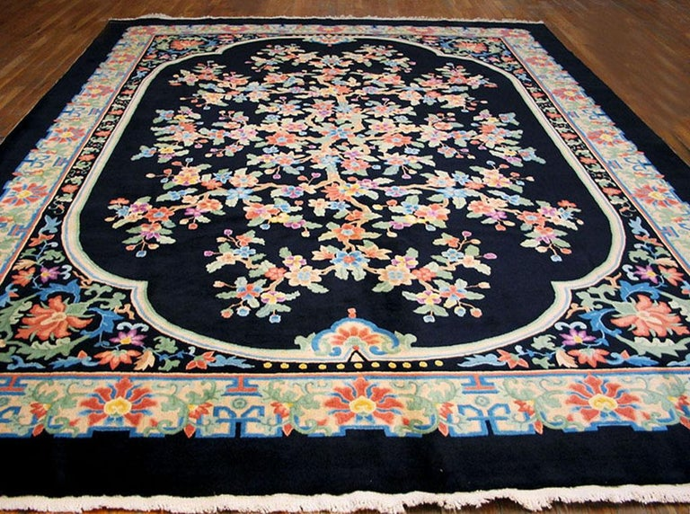 The black four lobed field barely contains an explosively flowering, branching major motif. The black palmette and arabesque corners, and the ivory paeony palmette and leafy arabesque main border are in a more stylized manner. This carpet was