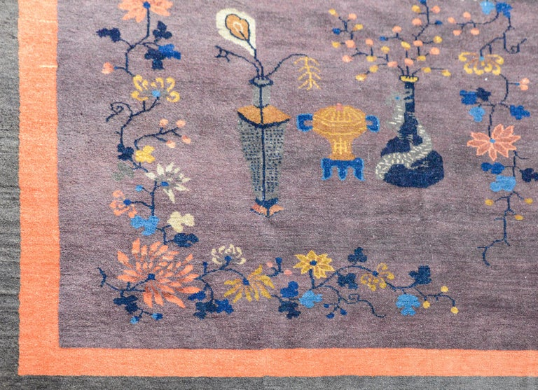 A gorgeous early 20th century Chinese Art Deco rug with pale violet field with scrolling vines containing myriad flowers and scholars objects, and surrounded by a thin inner orange stripe and a wide outer gray stripe border.