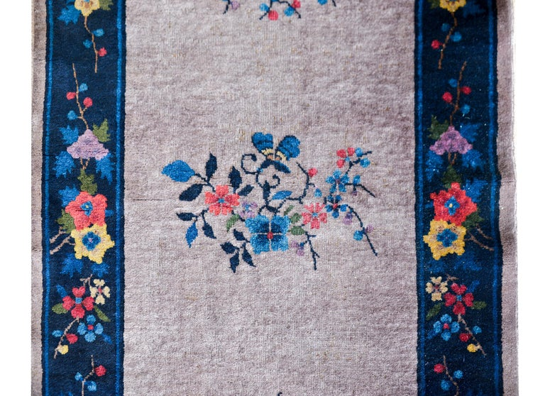 A wonderful Chinese Art Deco runner with a gray field with five multi-colored cherry blossom medallions surrounded by an indigo border with more multi-colored auspicious flowers including lotus, peonies, and more cherry blossoms.