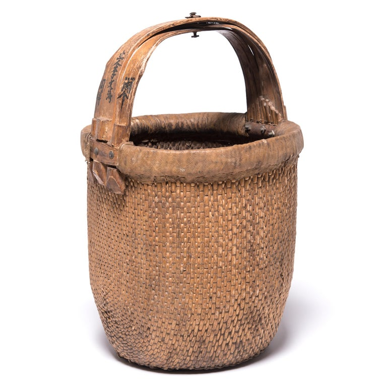 Basket making is an ancient and humble craft, but in the hands of a skilled weaver a simple willow basket can become a truly beautiful work of art. This bent handle basket is closely woven of fine willow strips for an evenly textured surface and