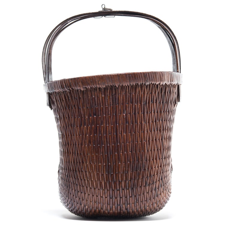 Basket making is an ancient and humble craft, but in the hands of a skilled weaver a simple willow basket can become a truly beautiful work of art. This bent handle basket was made in China long ago, and the artisan's mastery is evident: the strong,
